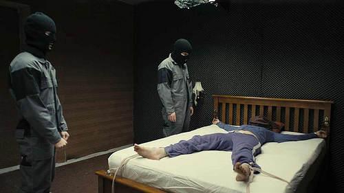 Les kidnappeurs et leur victime, allongée sur un lit