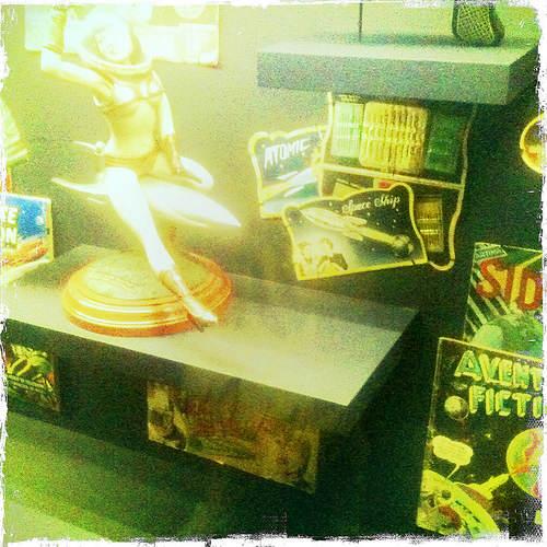 Photo d'une figurine représentant une femme montée sur un missile, entouré de tout un tas de comics et de gadgets