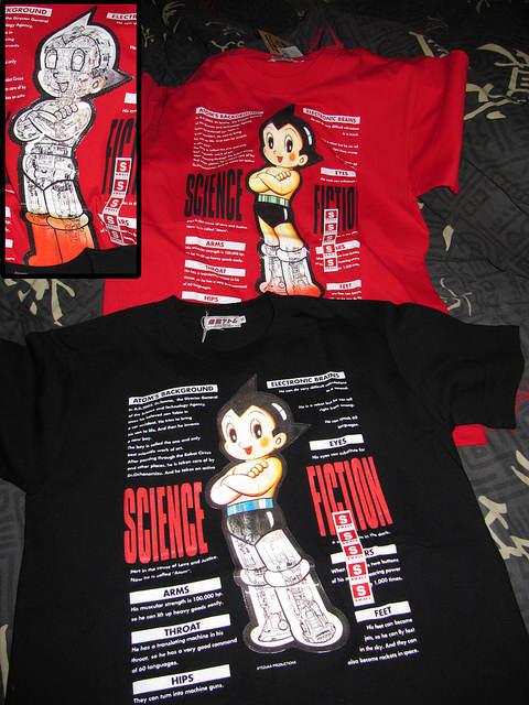 Photo des deux t-shirts, rouge et noir, avec l'image holographique
