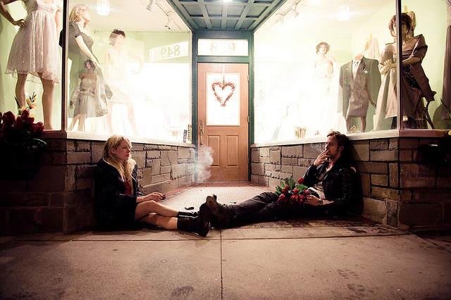 Photo tirée du film <em>Blue Valentine</em> montrant le couple, assis par terre l'un en face de l'autre,  entre deux vitrines de magasins,  en train de fumer.