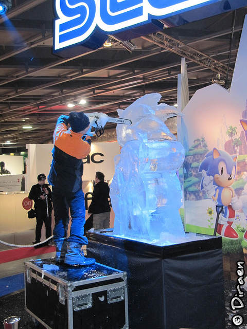 Photo du sculpteur maniant la tronçonneuse sur le bloc de glace