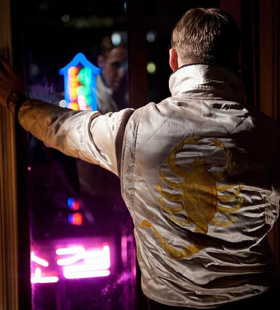 Le personnage principal est de dos, appuyé contre une fenêtre et l'on peut voir le scorpion dans le dos de sa veste