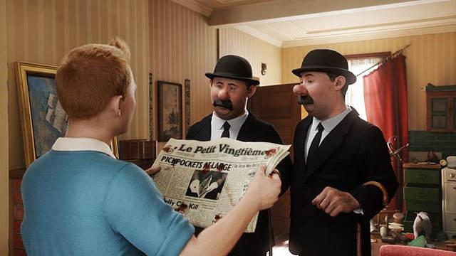 Tintin, face aux deux Dupont, tient un journal ouvert sur lequel on peut voir des traces de sang