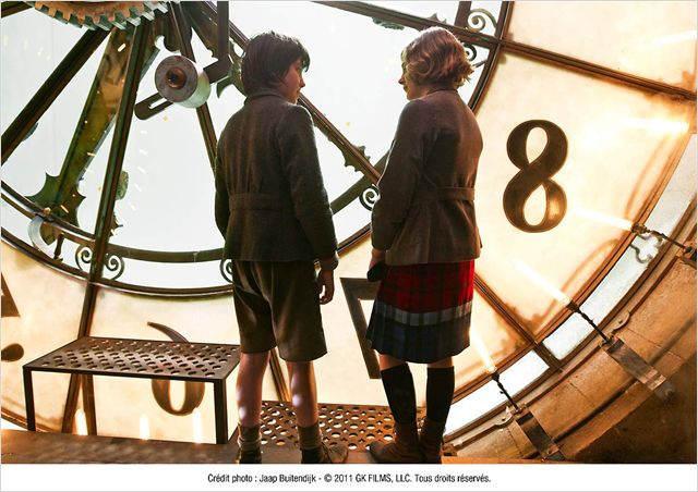 Les deux enfants, héros de l'histoire, se tiennent devant la grande horloge de la gare.