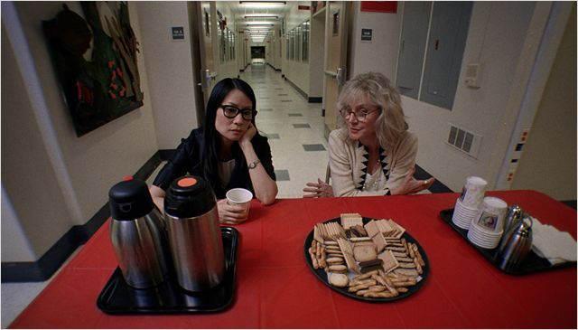 Au premier plan deux professeurs accoudées à une table couverte de gâteaux et de café, alors que derrière elles, le lycée est vide.