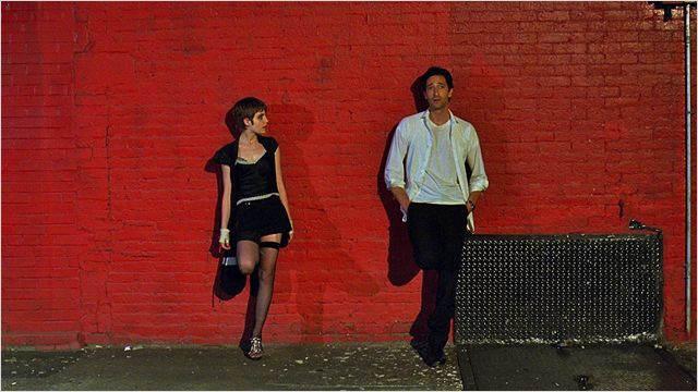 Le professeur est dos à un mur, à côté d'une jeune prostituée, également dos au mur et qui le regarde.