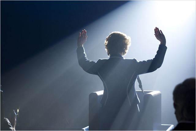 Margaret Thatcher de dos, saluant la foule lors d'un discours et baignant dans la lumière