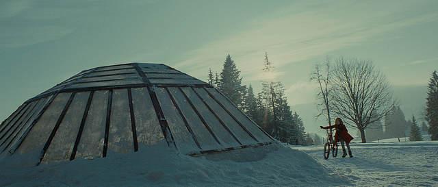 Eva et son velo à coté du dome de verre recouvert de neige