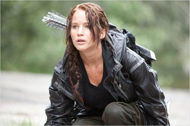 Katniss, accroupie et guettant quelque chose