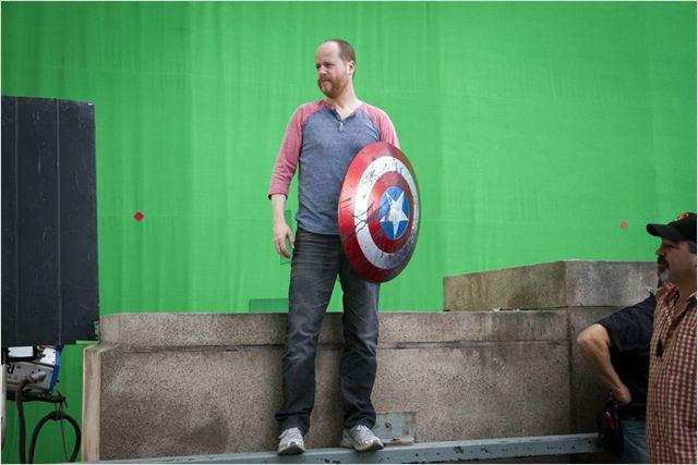 Joss Whedon tient le bouclier de Captain America devant un fond vert
