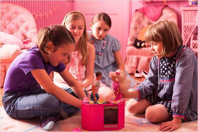 Les filles miment une scène avec des Barbie.