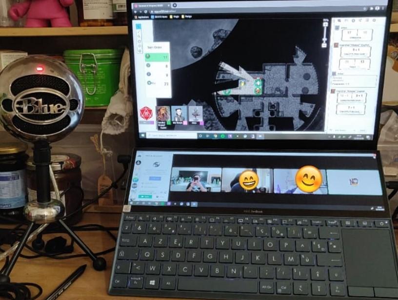 Photo d'un micro sur pied relié à un pc portable, affichant une carte de donjon. Le tout sur un plan de travail de cuisine
